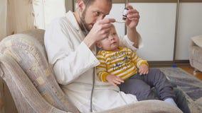 Der Doktor besucht den Babypatienten zu Hause Doktor gibt dem Baby Medizin von einem Löffel stock video footage