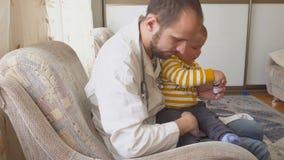 Der Doktor besucht den Babypatienten zu Hause Doktor gibt dem Baby Medizin von einem Löffel stock footage
