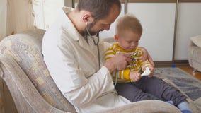 Der Doktor besucht den Babypatienten zu Hause Schätzchen mit Stethoskop stock video