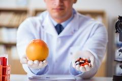 Der Doktor, der die Wahl zwischen gesundem und Vitaminen anbietet lizenzfreie stockbilder