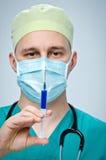 Der Doktor in einem grünen Hut und in einer Maske, die eine Spritze mit Medizin halten Lizenzfreie Stockbilder