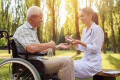 Der Doktor gibt dem alten Mann in einem Rollstuhl eine Pille Der alte Mann bereitet vor sich, sie anzunehmen Stockfotografie