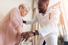 Der Doktor hilft, ein Bett eine ältere Frau in einem Pflegeheim zu verlassen lizenzfreies stockfoto