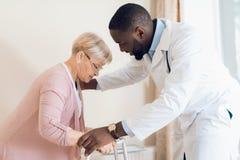 Der Doktor hilft, ein Bett eine ältere Frau in einem Pflegeheim zu verlassen stockbilder
