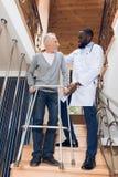 Der Doktor hilft einem Mann, die Treppe in einem Pflegeheim hinunterzugehen stockbild