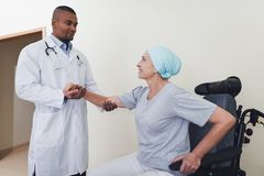 Der Doktor hilft einer Frau, das Rehabilitation durchmachen, nachdem Krebsbehandlung von einem Rollstuhl aufstehen stockbilder