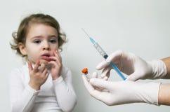 Der Doktor, der Injektionsspritze hält, Mädchen erschrak auf Hintergrund Lizenzfreie Stockfotografie
