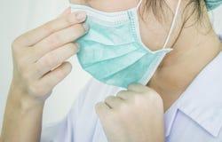 Der Doktor ist, entfernend tragend oder die Maske stockbild