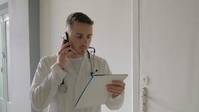Der Doktor ist am Telefon am Krankenhaus stock video footage
