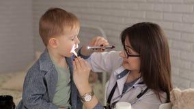 Der Doktor der Kinder überprüft die Kehle eines kranken kleinen Jungen mit einer hölzernen Spachtel stock footage