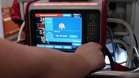 Der Doktor klickt an den Schirm des Elektrokardiographen, der an eine neugeborene Frühgeburt angeschlossen wird Krankenwagenauto- stock video footage