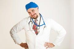 Der Doktor lächelt mit seinen Händen auf seinen Hüften stockfotografie