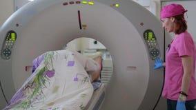 Der Doktor leitet eine ärztliche Untersuchung des Patienten, der ein tomographisches Gerät verwendet tomographie stock footage