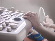 Der Doktor leitet eine Ultraschalldiagnose des Körpers stockfotografie