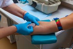 Der Doktor nimmt Blut von der Ader auf dem Arm Lizenzfreies Stockbild