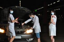 Der Doktor und die Krankenschwestern reparieren das Auto stockbilder
