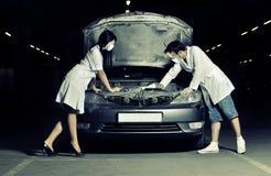 Der Doktor und die Krankenschwestern reparieren das Auto stockfotografie