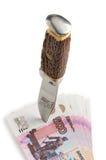 Der Dolch durchbohrt russische Rubel der Banknoten auf weißem Hintergrund Stockfotografie