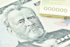 Der Dollarschein Vereinigter Staaten fünfzig, eine Makronahaufnahme mit Goldbarren Stockfotografie
