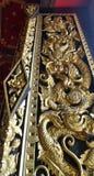 Der Drache, der auf Tempel windor Abdeckung mit thailändischem Kunstdesign mit Lack schnitzt, beschichtete wirkliches Goldblatt i Stockfotos
