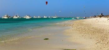 Der Drachen, der in die Karibischen Meere, Strandszene mit Hütten und Motor surft, yachts stockfotografie