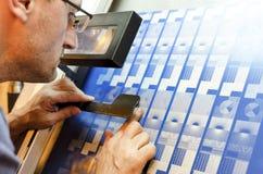 Der Drucker, der durch ein Augenglas schaut, um den Druck zu überprüfen, überzieht Kalibrierung lizenzfreies stockbild