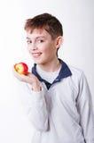 Der dunkelhaarige Junge, der einen roten Apfel hält Lizenzfreie Stockbilder