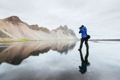 Der Ehemann ist eine Fotografstellung auf der Wasseroberfläche an der Küste von Island in Stokksnes stockfotos