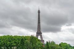 Der Eiffelturm, der über Bäumen mit stürmischen Wolken auftaucht Lizenzfreie Stockfotografie