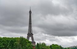 Der Eiffelturm über den Bäumen mit stürmischen Wolken Stockfotografie