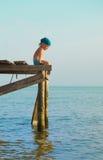 Der einsame Junge auf einem Ponton Stockbild