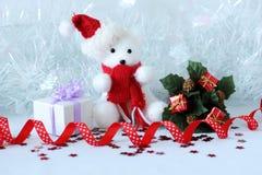 Der Eisbär, der einen Hut und einen blauen Schal trägt, warf nahe bei Geschenken mit glänzenden Knoten auf einem Weihnachtsfeiert Stockfoto