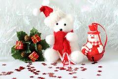 Der Eisbär, der einen Hut und einen blauen Schal trägt, warf nahe bei Geschenken mit glänzenden Knoten auf einem Weihnachtsfeiert Lizenzfreie Stockfotografie