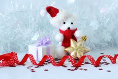 Der Eisbär, der einen Hut und einen blauen Schal trägt, warf nahe bei Geschenken mit glänzenden Knoten auf einem Weihnachtsfeiert Stockbilder