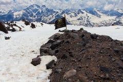 2014 07 der Elbrus, Russland: Mann schläft auf der Steigung vom Elbrus nahe der Flagge Stockbilder