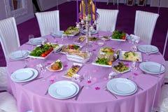 Der elegante Abendtisch Hochzeitstafel verziert mit Kerzen, gedient mit Tischbesteck und Tonware und mit einer Tischdecke bedeckt Stockfotos