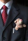 Der elegante stilvolle Geschäftsmann, der netten Teddybären in einer seiner Brustklagentasche hält Formales Verhandlungskonzept Stockfoto