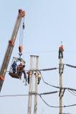 Der Elektriker, der auf Höhe schließen arbeitet vorbei, einen Hochspannungsdraht an Stockfotografie