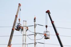 Der Elektriker, der auf Höhe schließen arbeitet vorbei, einen Hochspannungsdraht an Stockbild