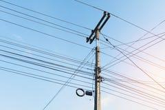 Der elektrische Pfosten mit schwarzem Drahtseil und blauem Himmel des freien Raumes Stockbild