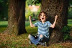 Der empörte Junge sitzt unter einem Baum mit Tablette auf Schoss Stockfoto