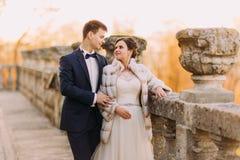 Der empfindliche Blickkontakt bewtween die glücklichen Jungvermähltenpaare, die nahe dem alten Zaun stehen Stockbild