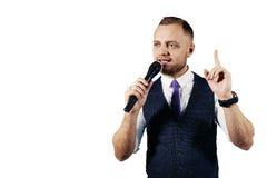 Der Entertainer Junger eleganter Unterhaltungsmann, der das Mikrofon, lokalisiert auf weißem Hintergrund hält stockfotografie