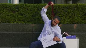 Der entlassene Mann sitzt auf der Straße und schnürt sich mit einer Bindungsvertretung, die jetzt es hart ist, zu leben, a ein stock video footage