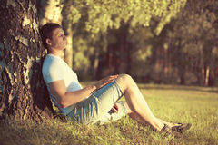 Der entspannende Mann, der unter einem Baum mit Augen sitzt, schloss das Meditieren, den warmen Abendsonnenuntergang im Profil ge Stockfotografie