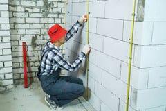 Der Erbauer, der auf seinem sitzt, bückt sich, Metallschienen auf Klammern auf Blockwand installierend lizenzfreie stockfotos