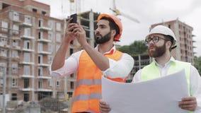 Der Erbauer und der Architekt auf Baustelle fotografierend mit samrtphone und mit Bauplan überprüfend stock video