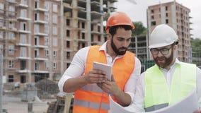 Der Erbauer und der Architekt auf Baustelle fotografierend mit der Tablettenarbeit und mit Bauplan überprüfend stock video footage