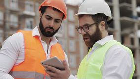 Der Erbauer- und Architektenmann besprechen den Bauplan des modernen Geschäftszentrums, das nahe steht stock footage