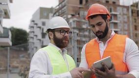 Der Erbauer- und Architektenmann besprechen den Bauplan des modernen Geschäftszentrums, das nahe steht stock video